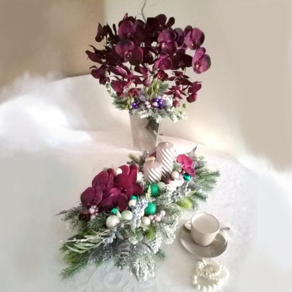 Fioletowy stroik na stół W tym uroczym Świątecznym stroiku wykorzystane materiały to między innymi ośnieżone gałązki, duże storczyki w przepieknym kolorze bakłażana, szklane szklane oraz dwie piękne srebrno-szare świece na drewnianej podstawie. Wszystkie kwiaty wykorzystane bukiecie to wysokiej jakości sztuczne kwiaty. Jest to elegancka alternatywa dla osób chcących w piękny sposób przyozdobic swój dom. Co więcej, do tej kompozycji możemy przygotować również inne elementy dekoracyjne, takie jak wieńce, stroiki, bukiety itp., zgodnie z Waszymi życzeniami, które możecie nam przekazać telefonicznie lub mailowo. Wymiary kompozycji Długość 70 cm Szerokość 34 cm, Zestaw świąteczny fioletowe bogactwo